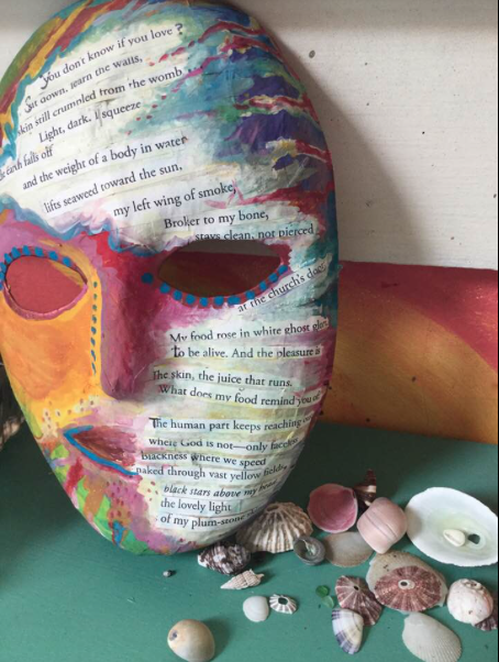 A papier mâché mask embossed with lines of poetry.